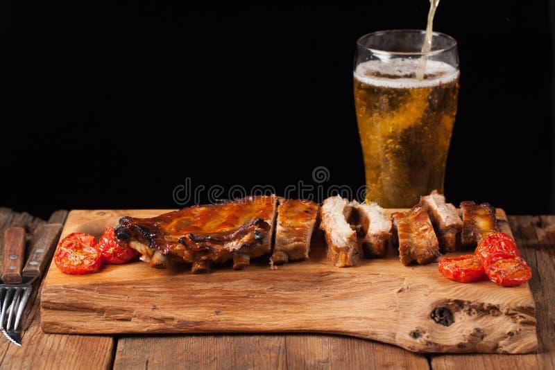 Las costillas de cerdo en salsa y miel de barbacoa cocieron los tomates en la tabla de madera vieja Carnes y cerveza ligera en fo imagen de archivo libre de regalías