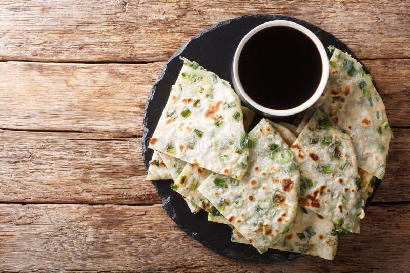 Las crepes de la cebolleta del vegano son un primer chino cacerola-frito curruscante del flatbread en un tablero visi?n superior  imagenes de archivo
