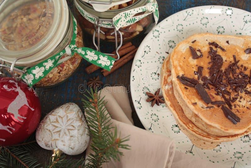Las crepes de la Navidad del trigo integral flour con el chocolate y la mantequilla, nueces, muesli, leche nutritivo, sano foto de archivo libre de regalías