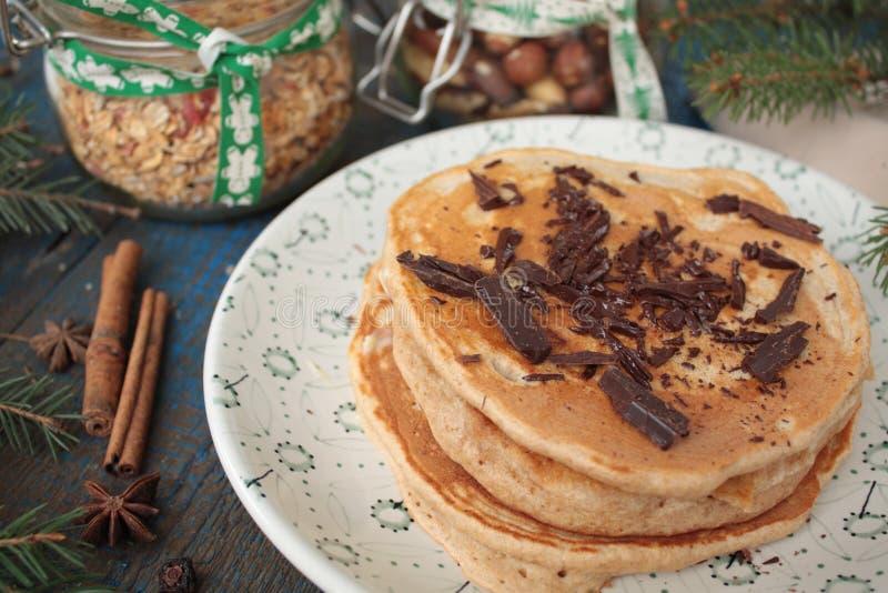Las crepes de la Navidad del trigo integral flour con el chocolate y la mantequilla, nueces, muesli, leche nutritivo, sano fotos de archivo