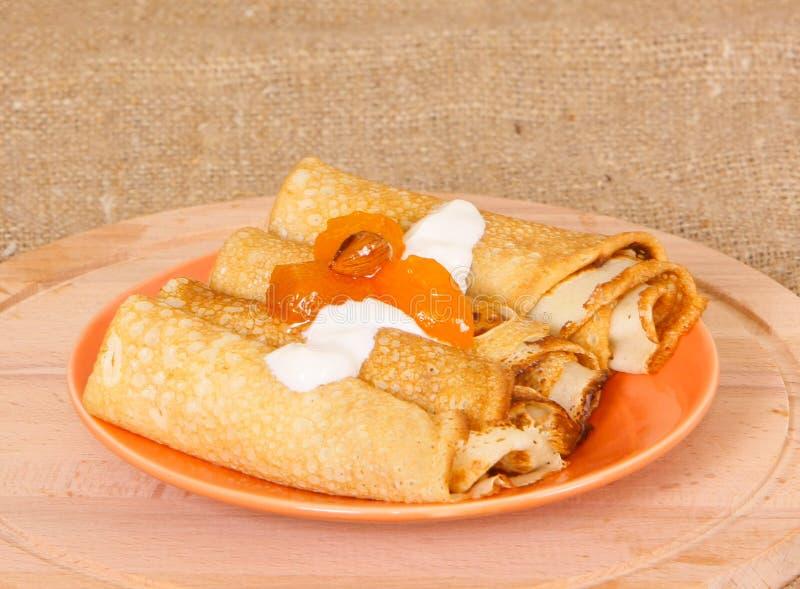 Las crepes fritas rodaron en un rollo con mentira del atasco y de la crema del albaricoque en una placa anaranjada imagenes de archivo