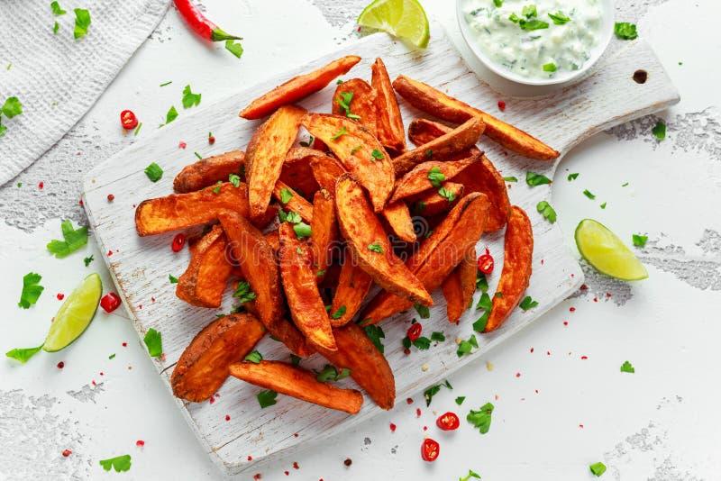 Las cuñas anaranjadas cocidas hechas en casa sanas de la patata dulce con la inmersión poner crema fresca sauce, las hierbas, sal imagen de archivo