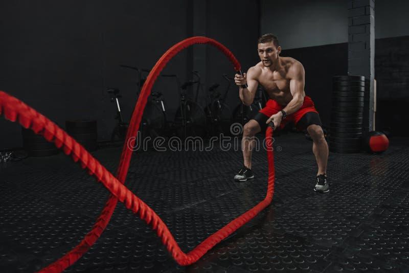 Las cuerdas de la batalla de Crossfit ejercitan durante el entrenamiento del atlete en el gimnasio del entrenamiento