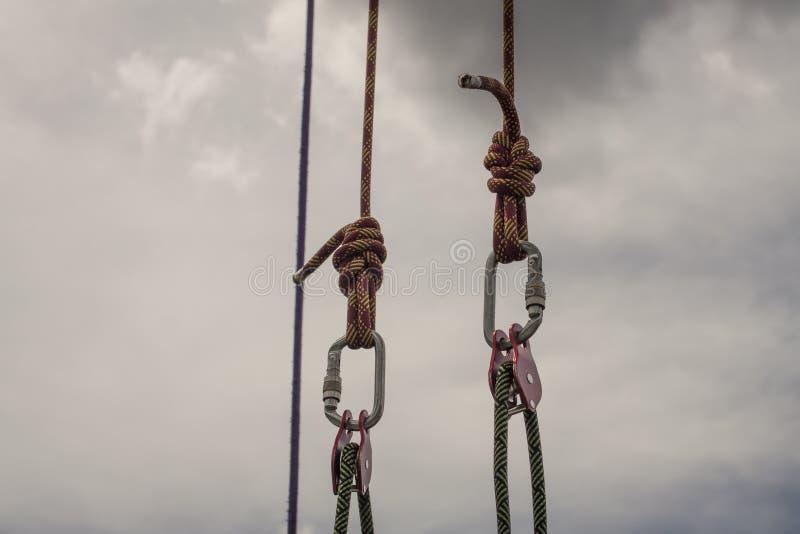 Las cuerdas flojas conectaron por las carabinas contra el fondo gris del cielo fotografía de archivo libre de regalías