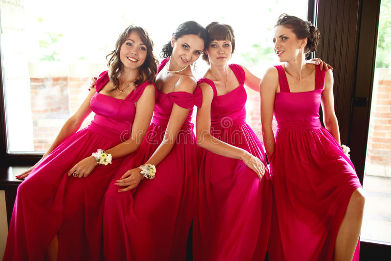 Las damas de honor bonitas en vestidos rosados se sientan detrás de una ventana grande fotos de archivo libres de regalías