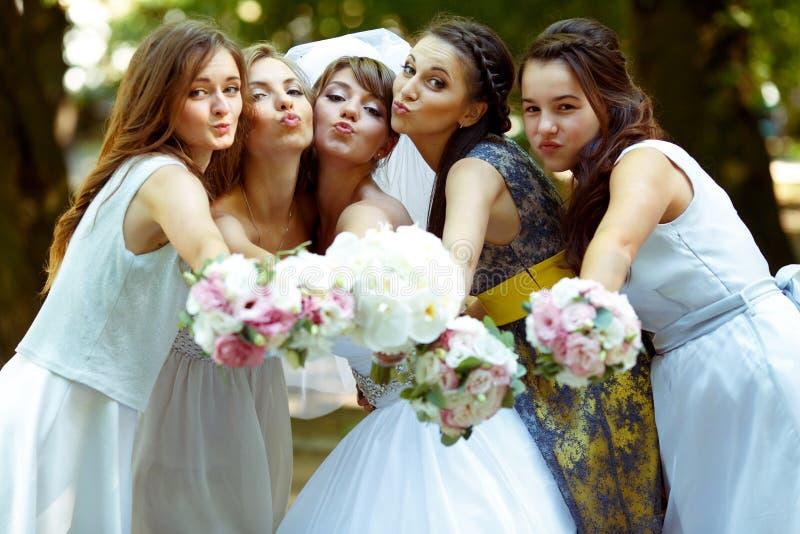 Las damas de honor bonitas rodean a una novia que sostiene ramos de la boda adentro imagenes de archivo