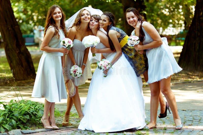 Las damas de honor se inclinan a la novia mientras que presentan en el parque fotos de archivo