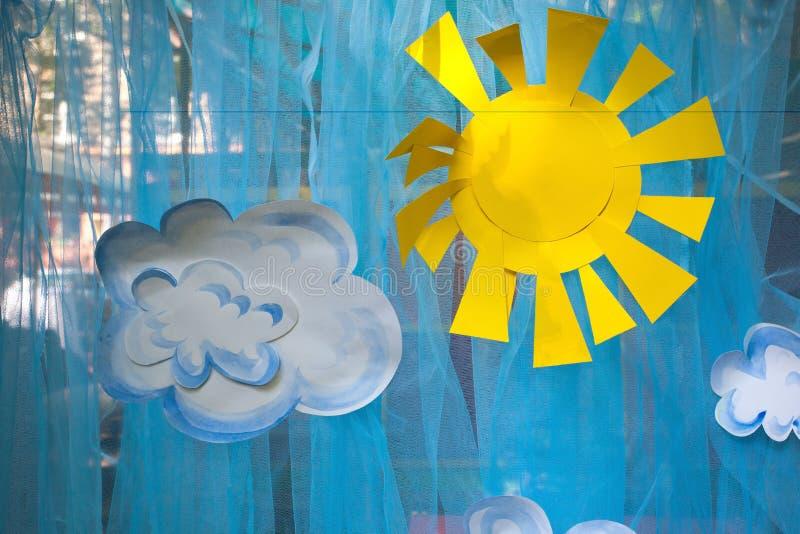 Las decoraciones de appliques, del sol de papel y de nubes fotografía de archivo
