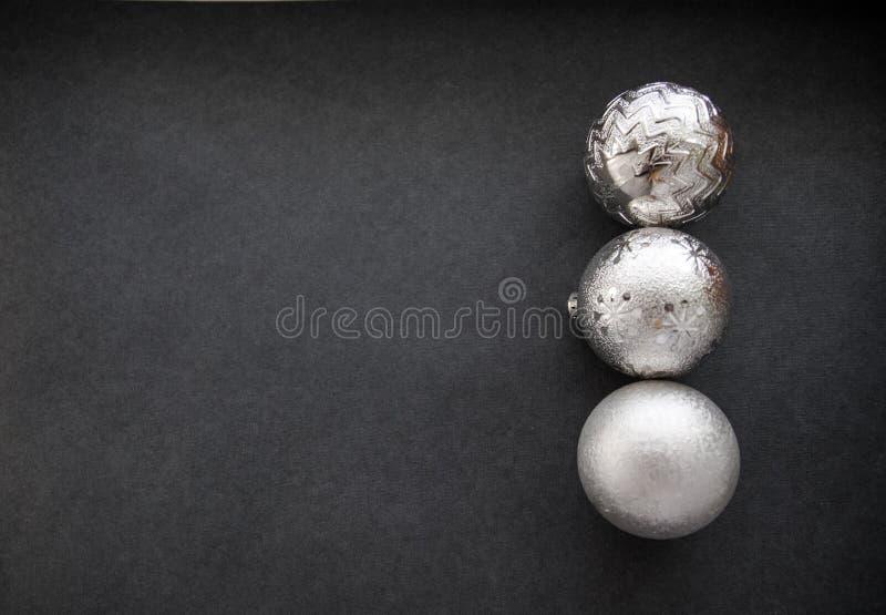 Las decoraciones del árbol de navidad platean tres bolas en fondo gris foto de archivo libre de regalías