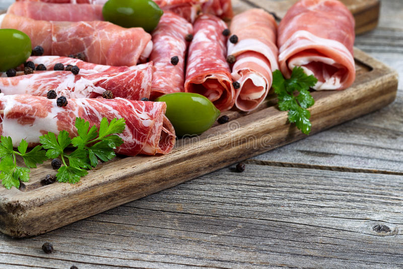 Las diversas carnes crudas en la porción suben con el fondo rústico foto de archivo