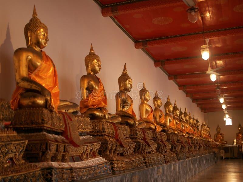 Las diversas estatuas de Buda que se colocan en fila fotos de archivo