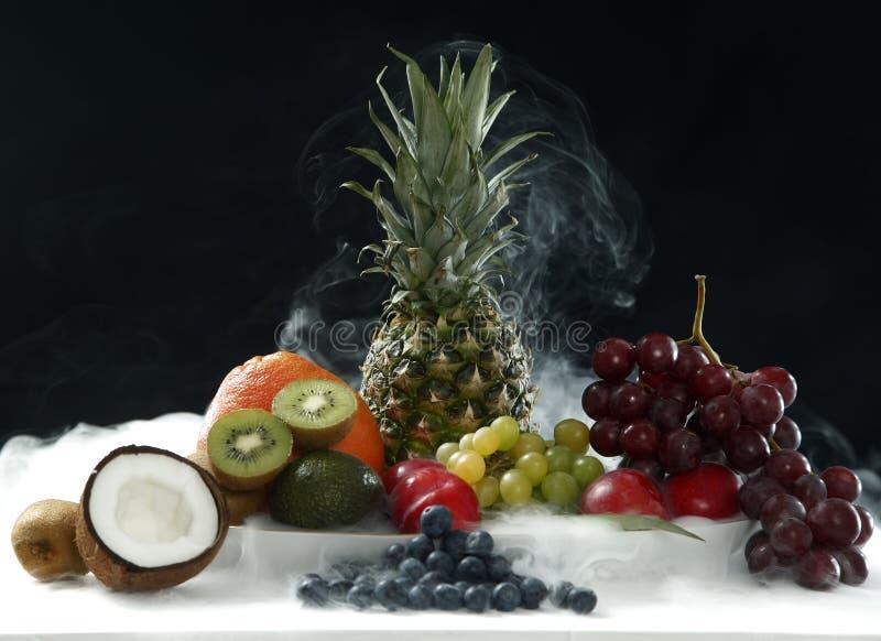 Las diversas frutas frescas del coco, de la piña, de maduro, las manzanas y uva en la tabla blanca en fondo negro en humo se vapo fotos de archivo