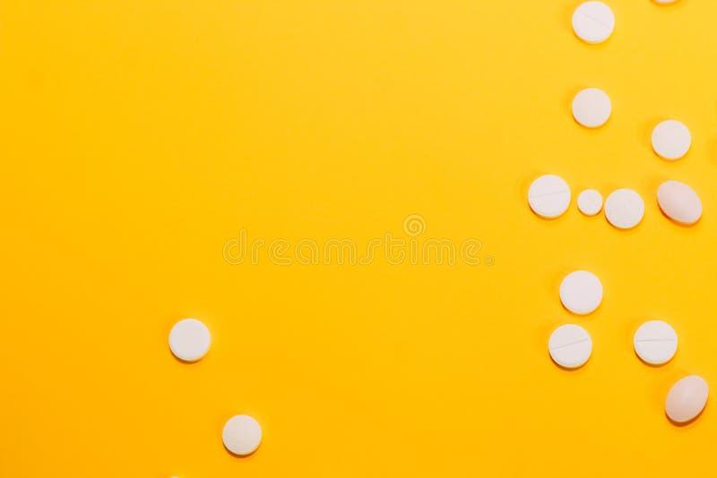 Las diversas píldoras y vitaminas se dispersan en un fondo amarillo Espacio para el texto foto de archivo libre de regalías