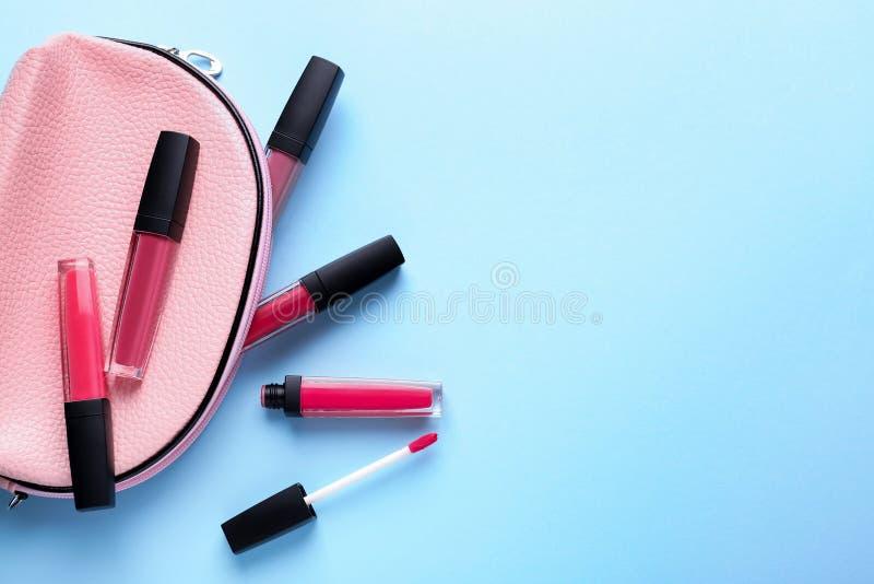 Las diversos barras de labios y cosméticos líquidos empaquetan en fondo del color imagen de archivo libre de regalías