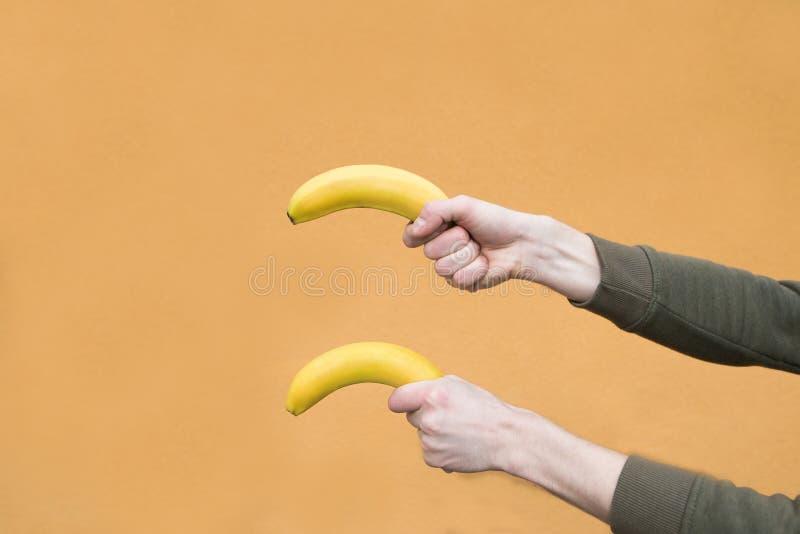 Las dos manos de los hombres sostienen dos plátanos contra la perspectiva de una naranja imagen de archivo