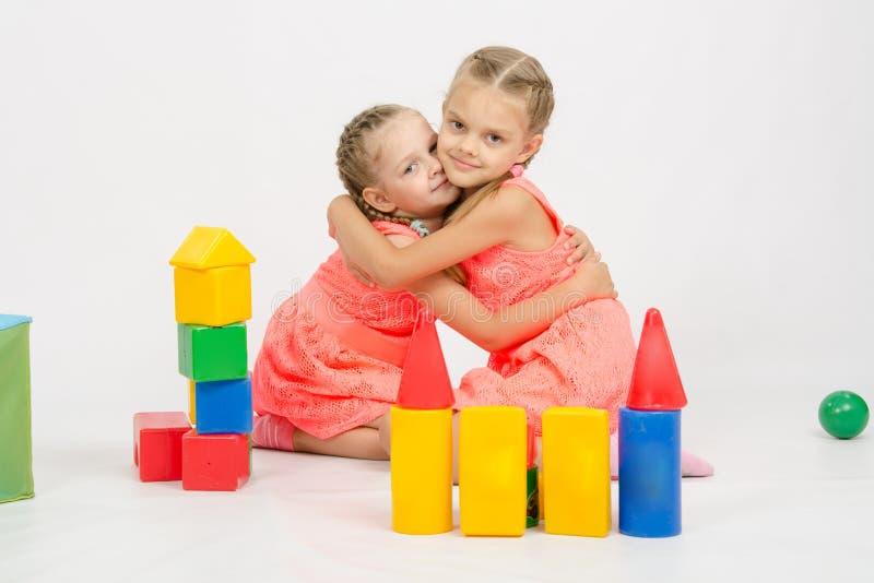 Las dos muchachas felices abrazan la construcción de un castillo fuera de bloques fotos de archivo