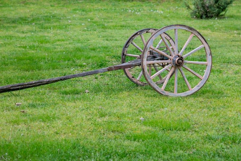 Las dos ruedas viejas cart la base en campo verde fotografía de archivo libre de regalías