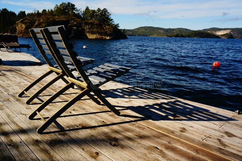 Las dos sillas de madera grises acercan al fiordo, Noruega fotografía de archivo libre de regalías