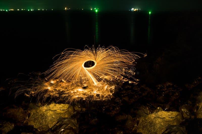 Las duchas del hombre de brillar intensamente chispean de las lanas de acero de giro en rocoso foto de archivo libre de regalías