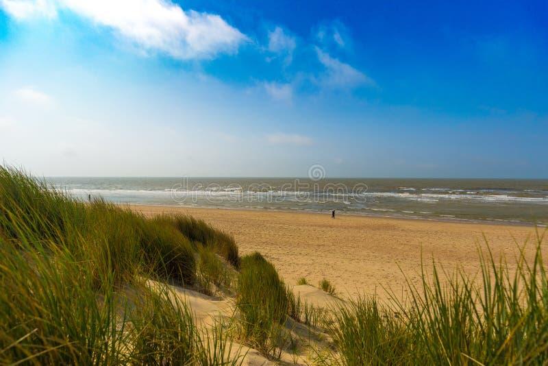 Las dunas en Mar del Norte belga costean contra las nubes del cirro y de estrato y la hierba de lámina foto de archivo