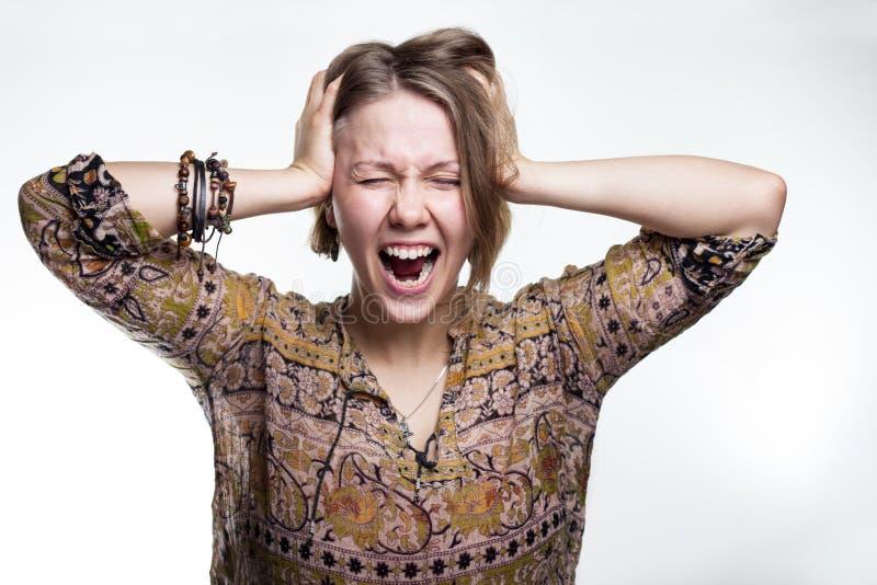 Las emociones son tensión, locura grito loco del concepto mujer que arranca su pelo adolescente natural que grita con los ojos ce fotos de archivo libres de regalías