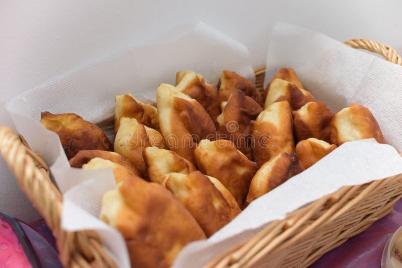 Las empanadas fritas apetitosas, frescas, recientemente cocinadas mienten en la cesta de madera, colocándose en la tabla imagen de archivo libre de regalías