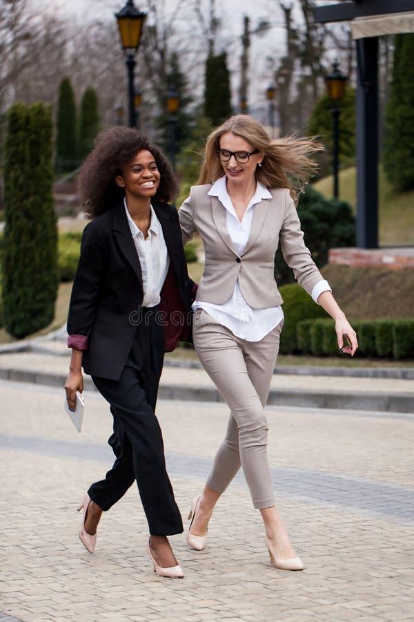 Las empresarias africanas y bastante caucásicas encantadoras son de risa y sonrientes mientras que caminan a lo largo del parque fotos de archivo libres de regalías