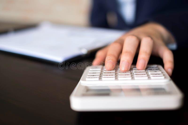 Las empresarias calculan la renta del negocio de exportaci?n en la tabla de madera Concepto del asunto imagen de archivo libre de regalías