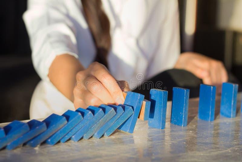Las empresarias dan la detención de efecto de dominós de madera descendente de haber derribado continuo o la arriesgan foto de archivo