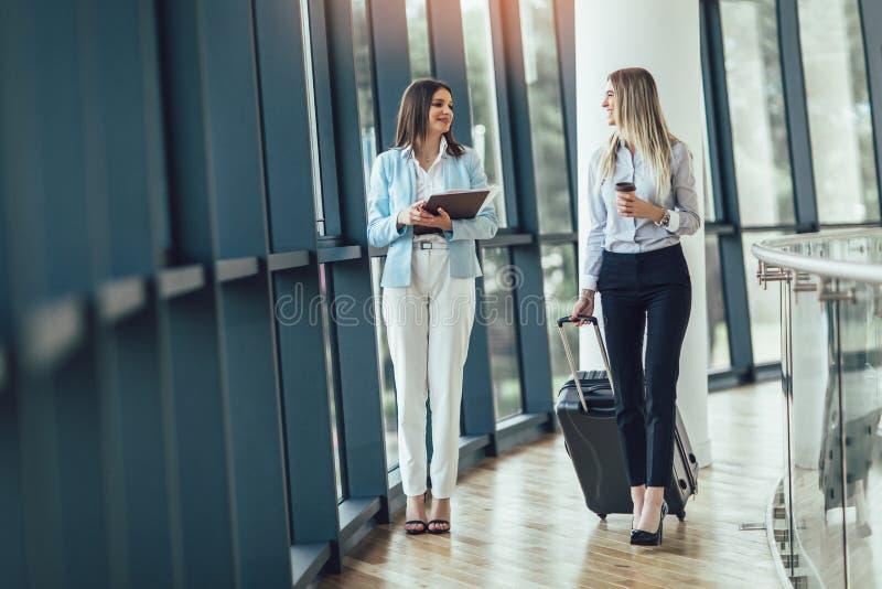 Las empresarias jovenes llevan a cabo viaje del equipaje al viaje de negocios imagen de archivo