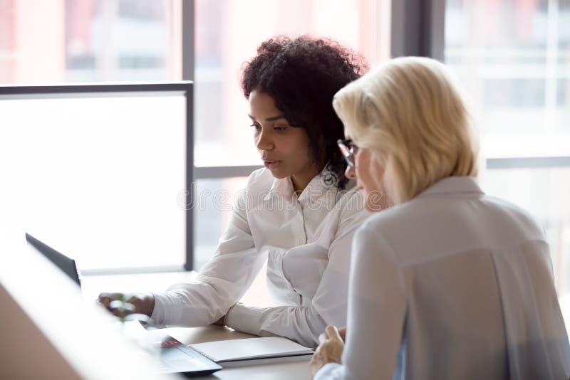 Las empresarias jovenes y viejas diversas serias trabajan juntas en el ordenador portátil imagen de archivo libre de regalías