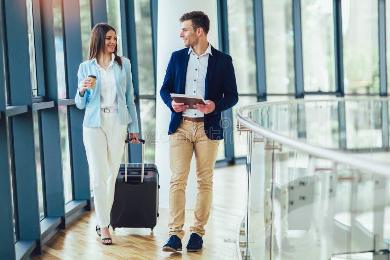 Las empresarias llevan a cabo viaje del equipaje al viaje de negocios fotos de archivo