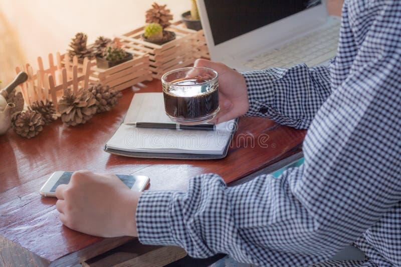 Las empresarias que usan el funcionamiento del teléfono móvil y sostienen una taza de café en cafetería foto de archivo