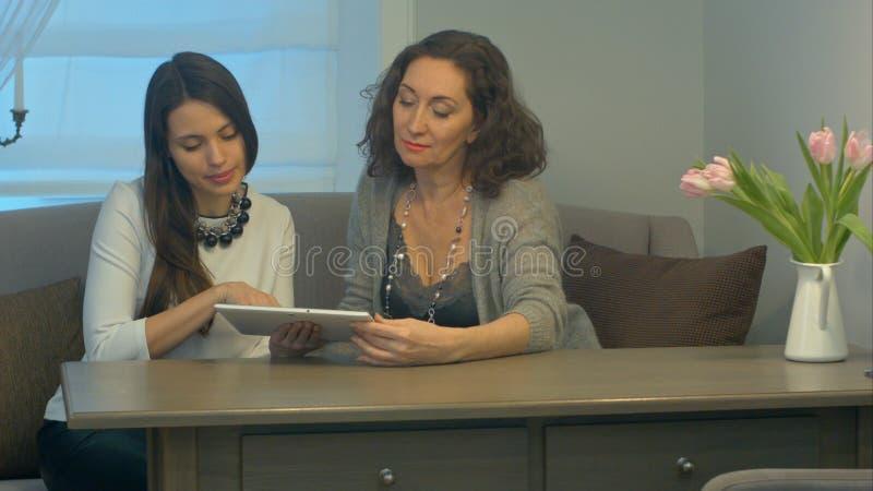 Las empresarias sientan y tienen reunión informal que mira datos sobre la tableta digital juntos foto de archivo