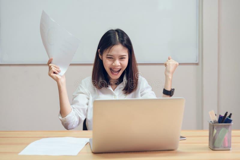Las empresarias son felices de tener éxito en trabajo, y muestran el documento en la tabla en fondo del offiec foto de archivo