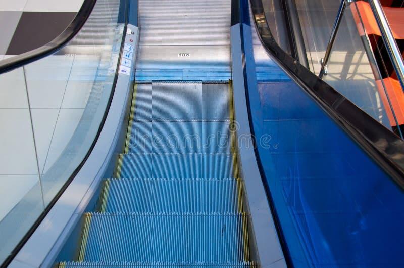 Las escaleras de la escalera móvil tragan la barandilla azul fotos de archivo