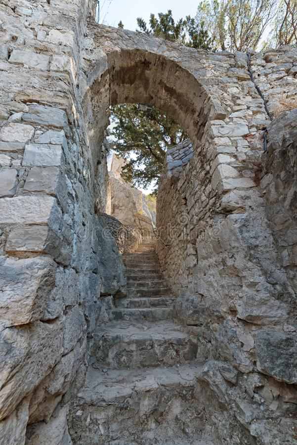 Las escaleras y el arco de piedra estrechos al Mirabella se escudan Croacia imagenes de archivo