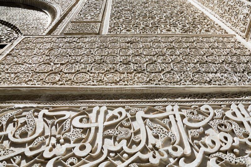 Las escrituras complejas en árabe y trabajo sobre las paredes de Bou Inania Madarsa en Fes, Marruecos imágenes de archivo libres de regalías