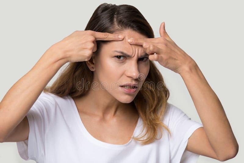 Las espinillas descontentas del apretón de la mujer que miran la cámara sienten enojadas fotos de archivo