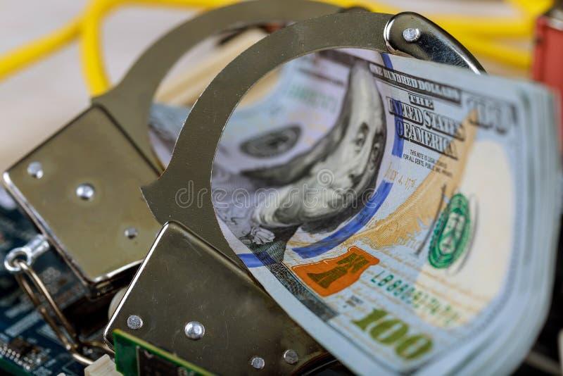 las esposas en una pila de dinero de los dólares esposan delito informático imagen de archivo libre de regalías