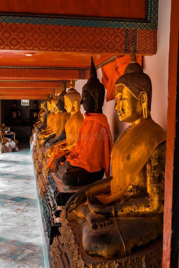 Las estatuas de oro de Buda con la naranja congriegan Surat Thani Tailandia imagen de archivo