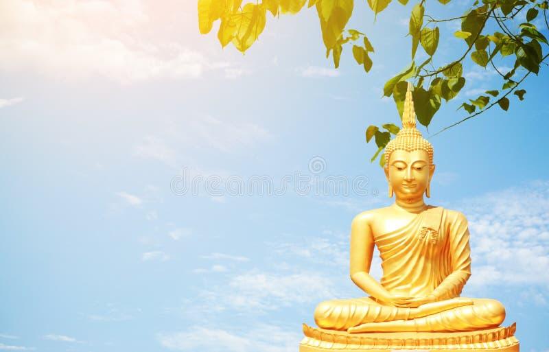 Las estatuas de oro de Buda en fondo del cielo foto de archivo