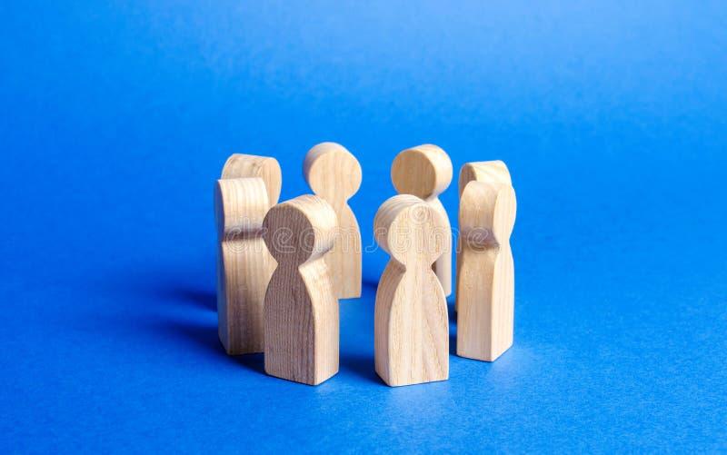 Las estatuillas de la gente se colocan en un círculo discusión, cooperación Informe de los empleados Organización de trabajo y de imagen de archivo