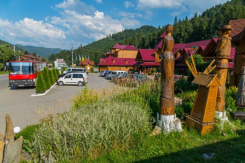 Las estatuillas hermosas tallaron de un árbol cerca de un café del borde de la carretera situado cerca de las montañas imagen de archivo