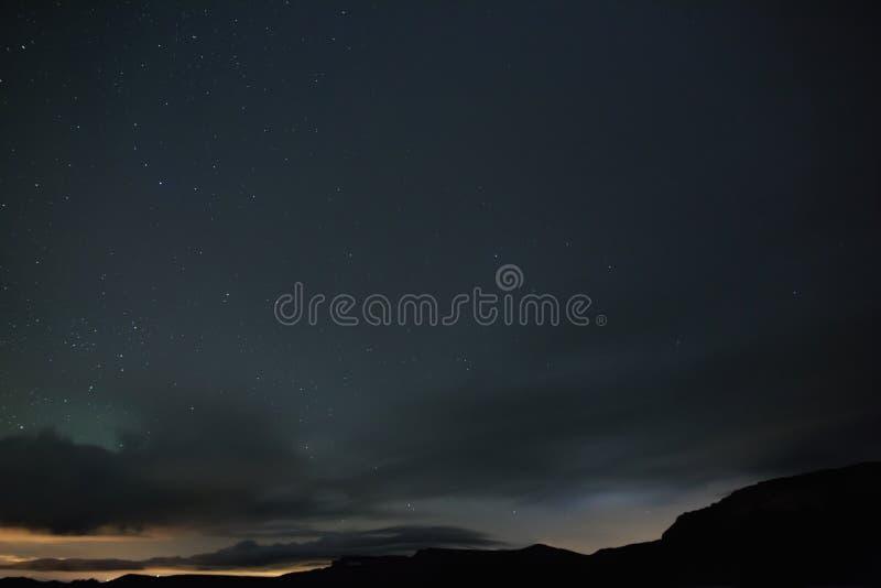 Las estrellas brillantes brillan a través de las nubes en el cielo nocturno fotos de archivo libres de regalías