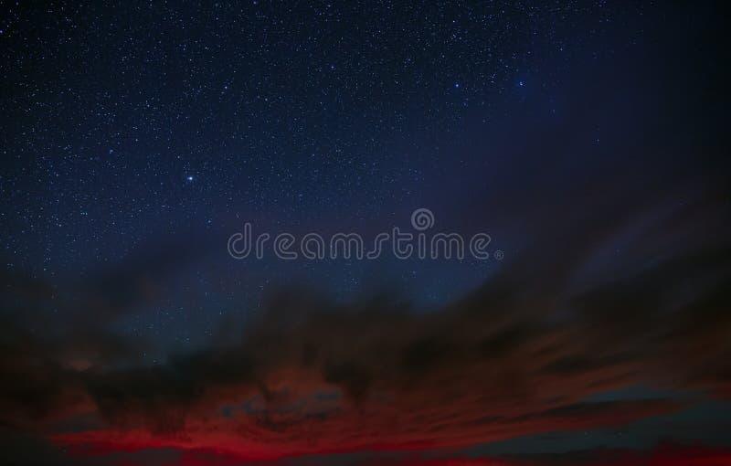 Las estrellas brillantes brillan a través de las nubes en la noche fotos de archivo libres de regalías
