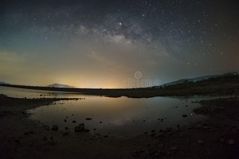 Las estrellas en el cielo reflejan la luz en la noche La vía láctea sobre las montañas y la charca Mae Prachan Dam y depósito, Ph fotos de archivo libres de regalías