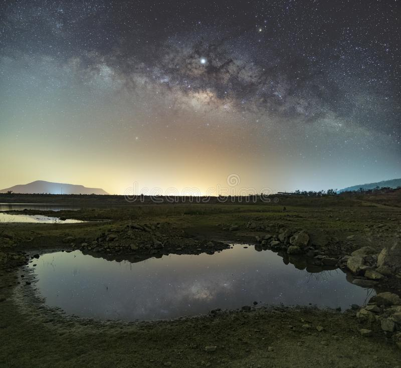 Las estrellas en el cielo reflejan la luz en la noche La v?a l?ctea sobre las monta?as y la charca fotografía de archivo