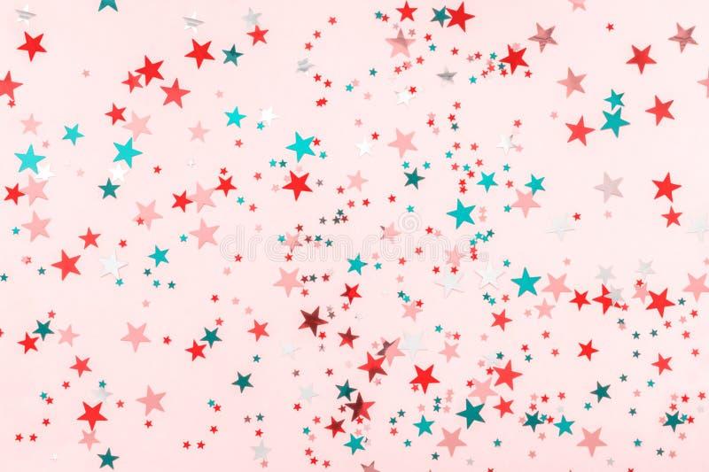 Las estrellas multicoloras brillan en fondo rosado Contexto festivo del pastel del d?a de fiesta Concepto de la celebraci?n La Na fotografía de archivo
