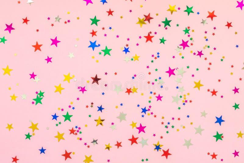 Las estrellas multicoloras brillan en fondo rosado Contexto festivo del pastel del d?a de fiesta Concepto de la celebraci?n Visi? imagen de archivo libre de regalías